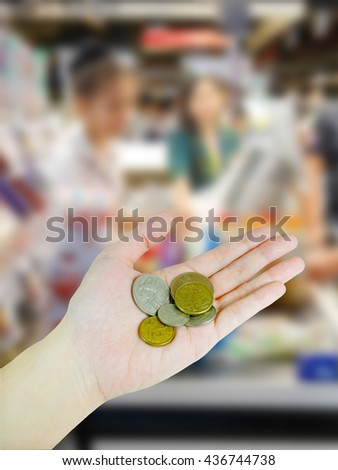 Woman's hand holding Australian coins on supermarket background - stock photo
