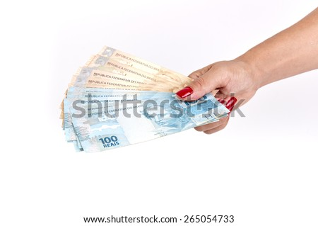 Woman's hand holding Brazilian money on white background