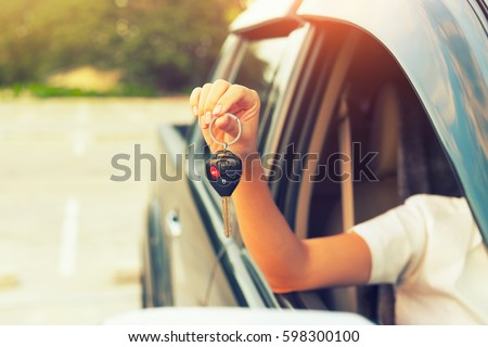 Woman's hand holding car key.