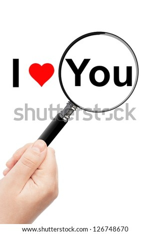 Woman's hand, holding classic styled magnifying glass, with I Love You sign - stock photo