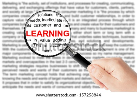 Woman's hand, holding classic styled magnifying glass, with Learning sign