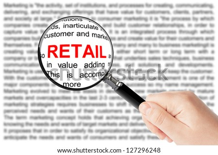 Woman's hand, holding classic styled magnifying glass, with Retail sign - stock photo