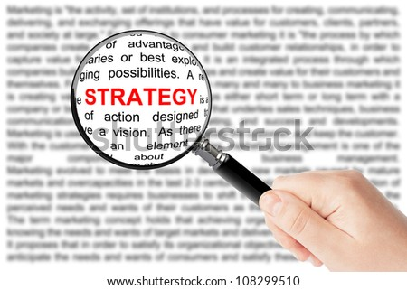 Woman's hand, holding classic styled magnifying glass, with strategy word - stock photo