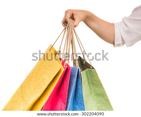 Woman's hand holding colored shopping bags on white background. Close-up. - stock photo