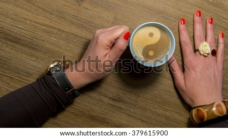 woman's hand holding cup of coffee with yin yang sign