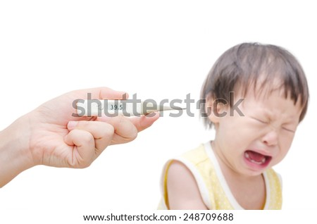 Woman's hand holding digital thermometer and crying baby sitting in background - stock photo