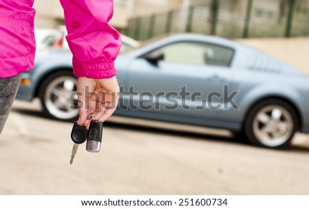 Woman's hand holding modern car keys ready for rental - Concept of transportation with automobile second hand sale and trade - stock photo
