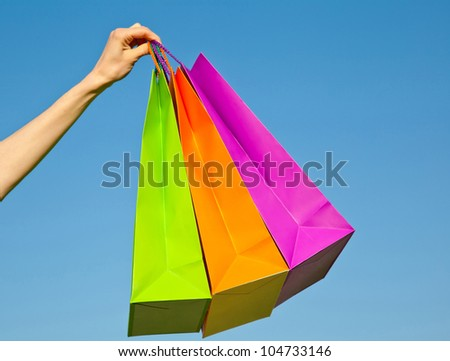 Woman's hand holding multicolored paper bags against blue sky