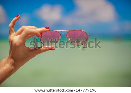 Woman's hand holding pink sunglasses on tropical beach background the sea