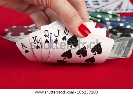 Woman's hand holding playing cards royal flush