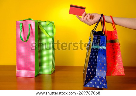 Woman's hand holding shopping bags and credit card on yellow background   - stock photo
