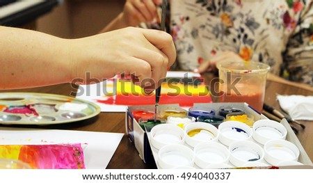 woman's hand holding the brush with paint, concept learning drawing