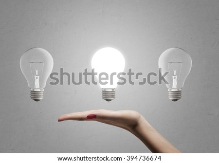 Woman's hand holding three light bulbs without touching them - stock photo