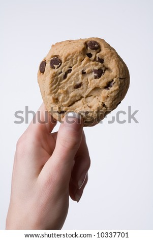 Woman's hand holding up a cookie - stock photo