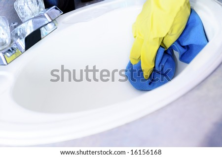Woman's hand in latex glove cleaning the lavabo with microfibre cloth - stock photo