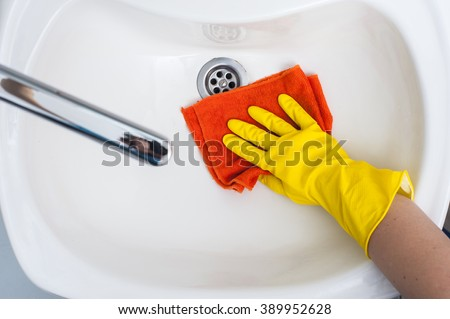 Woman's hand in yellow rubber glove wiping a sink. Cleaning concept. - stock photo
