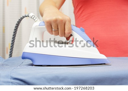 Woman's Hand Ironing Shirt On Ironing Board