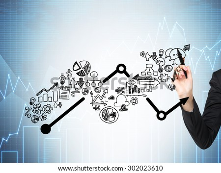 Woman's hand is drawing a growing arrow. Business icons as an integral part of the growing graph. Charts on the background. - stock photo