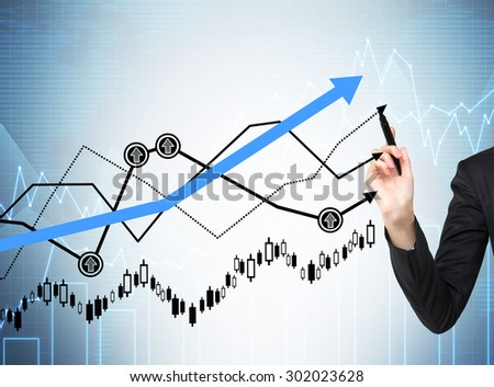 Woman's hand is drawing a growing graphs. Forex chart on the background.