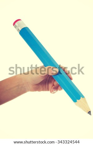 Woman's hand is holding big pencil.