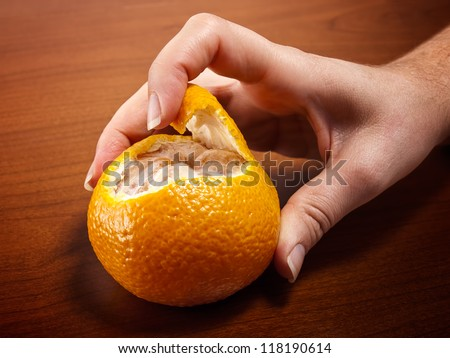 Woman's hand is peeling a tangerine on a wooden background. - stock photo