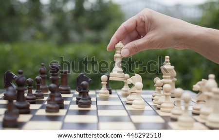 woman's hand moves a wooden piece of queen on the chessboard with other chess pieces on the green background of nature