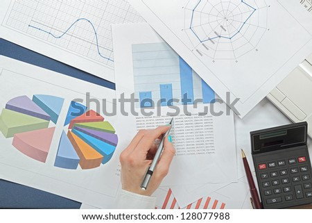 woman's hand over pages with stats - stock photo