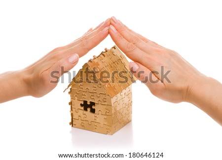 woman's hand over the home of gold color isolated on white background - real estate loan or insurance concept - stock photo
