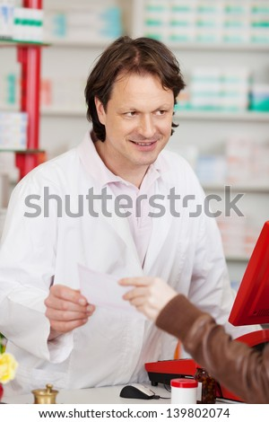 Woman's hand passing prescription paper to male pharmacist