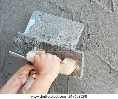 Woman's hand plastering a wall with trowel.  - stock photo