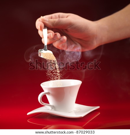 woman's hand pouring brown sugar in white cup of coffee on red background - stock photo