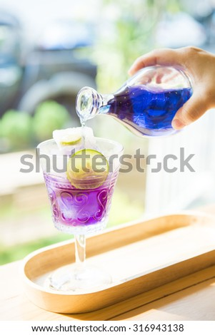 woman's hand pouring pea flower water into a glass, fresh