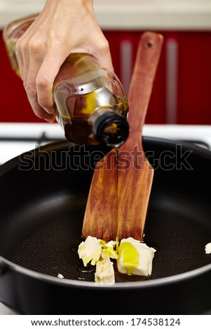 Woman's hand pouring virgin olive oil over melting butter in the hot pan