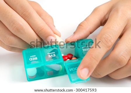 Woman 's hand putting a capsule into a pill dispenser
