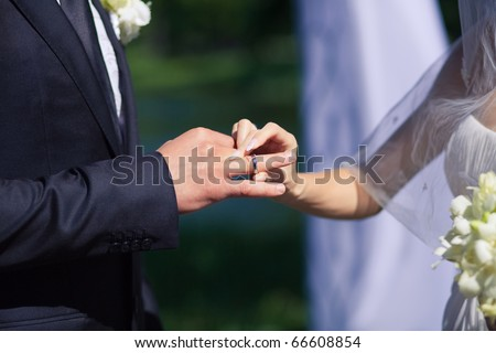 woman's hand putting a wedding ring on the grooms finger