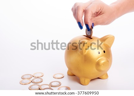 Woman's hand putting coins of the Brazilian money into piggy bank in white background. Save money or investment concept.
