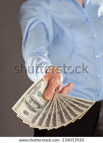 Woman's hand reaching out money on grey background - stock photo