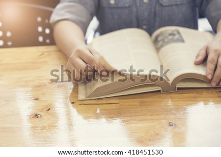 woman's hand reading book on wooden table, selective focus and vintage tone