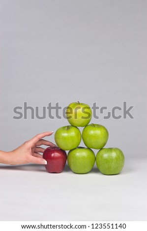 Woman's hand selecting the only red apple from a stack of mostly green apples - stock photo