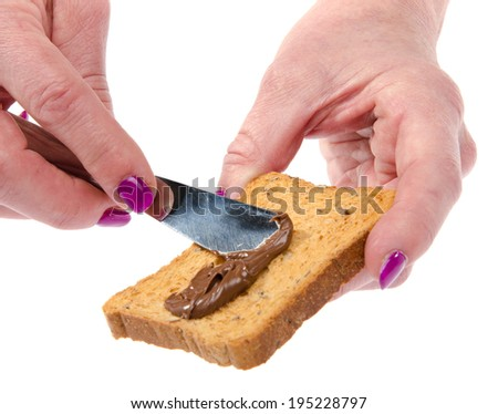 Woman's hand spreading hazelnut spread on a toast, isolated on white