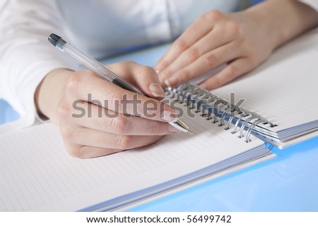 Woman's hand starting to make notes in a diary - stock photo