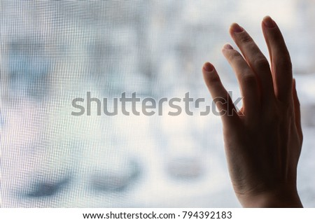 woman's hand touches the window