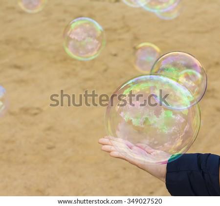 Woman's hand touching soap bubble - stock photo