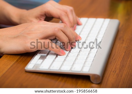 Woman's hand typing on computer keyboard - stock photo