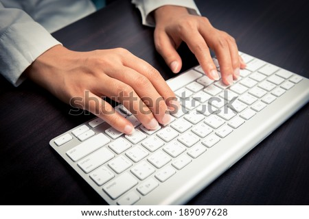 Woman's hand typing on computer keyboard closeup