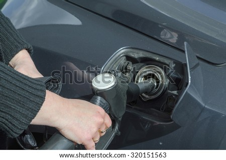 Woman's hand when fueling a sports car with fuel E10