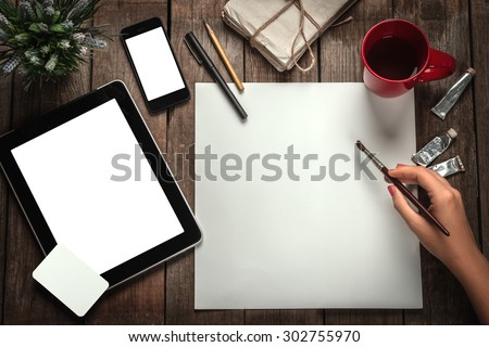 Woman's Hand With A Brush Paints On A Paper. Tablet Computer, Phone And Business Cards On A Wooden Table - stock photo