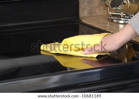 Woman's hand with a cloth cleaning ceramic cooktop - stock photo