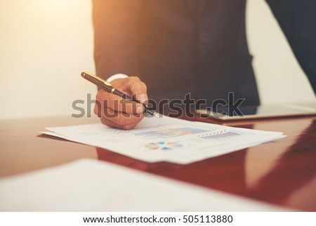 Woman's hand with a pen writing on the business paper. Report chart,busy at work.