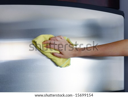 Woman's hand with microfiber cloth polishing a stainless steel fridge door